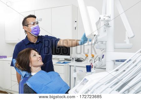 Dentist Explaining Xray On Screen To Female Patient