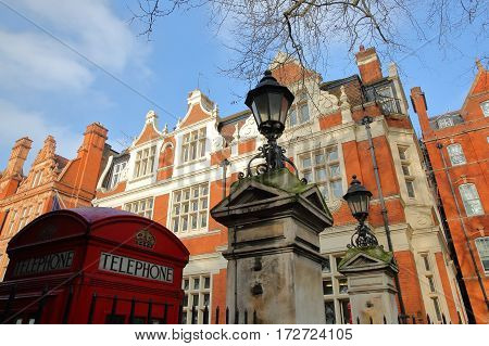 LONDON, UK - FEBRUARY 13, 2017: The entrance of Mount Street Gardens (borough of Westminster) with Red brick Victorian houses facades in the background and a Telephone Red Box in the foreground