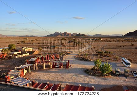 SOSSUSVLEI NAMIBIA - JAN 30 2016: Entrance in the Sossusvlei Lodge and area around. View from above at sunset. The most popular place in Namib-Naukluft park.