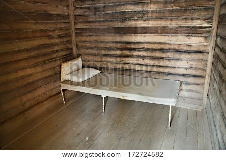 Old wooden prison cell with simple bed
