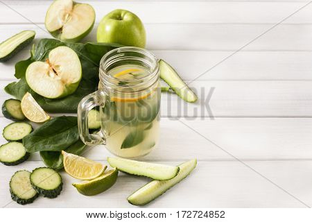 Detox cleanse drink background. Lemonade smoothie ingredients. Natural healthy juice in glass jar for diet or fasting day. Cucumber, apple, lime and spinach mix on white wood top view with copy space
