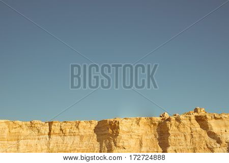 cliff of the yellow orange brown sand soil clay under the bright sunny day with deep blue sky.