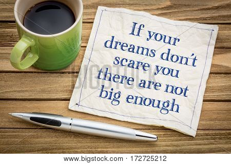 If your dreams don't scare, there are not big enough - handwriting on a napkin with a cup of espresso coffee