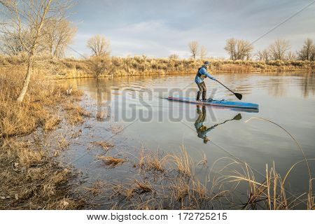 WInter or early spring training on a racing stand up paddling, a calm in Arapaho Bend Natural Area, Fort Collins, Colorado