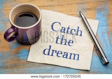 Catch the dream inspirational handwriting on a napkin with a cup of espresso coffee