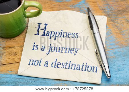 Happiness is a journey, not a destination - handwriting on a napkin with a cup of espresso coffee
