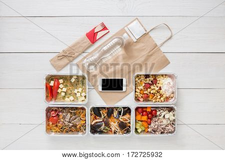 Healthy restaurant food, mockup for internet online order background. Fresh diet daily meals delivery. Vegetables, seafood, meat and fruits in foil box. Top view, flat lay on wood, copy space
