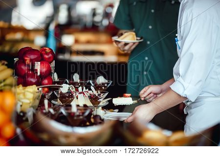 The chef puts on a plate slice of cheesecake for the guest at the restaurant buffet close up hands
