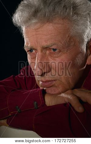 portrait of a  pensive senior man  over a black  background