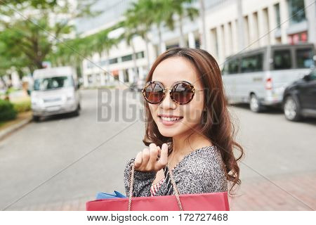 Happy young woman in the city with paper bags