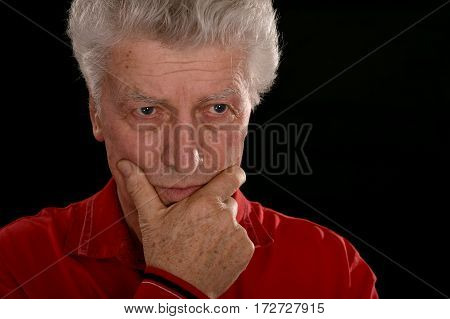 sad old man in red on a black background