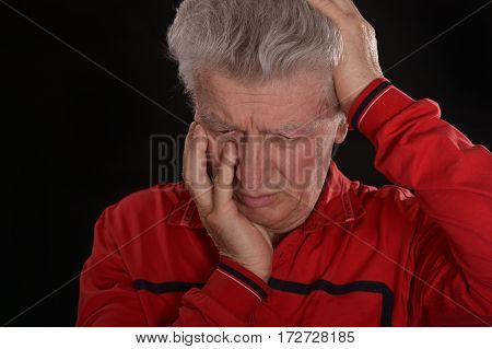 sad mature man in red on a black background