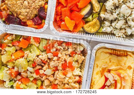 Healthy food background. Take away of natural organic meals in foil boxes. Fitness nutrition, meat, vegetables and fruits. Top view, flat lay. Restaurant dishes delivery