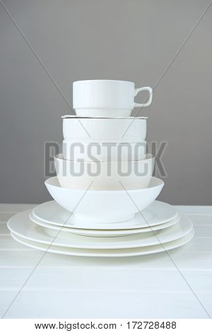 Minimalist picture of white porcelain kitchenware made of different size and shape plate and bowls piled up