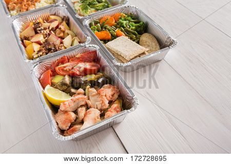 Healthy food background. Take away of natural organic meals in foil boxes. Fitness nutrition, salmon fish, fruits and steamed vegetables. Restaurant dishes delivery