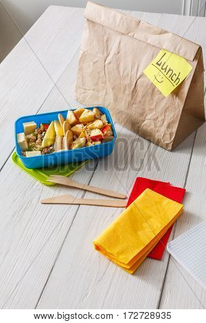Healthy school lunch for child or teenager. Craft paper package and food in lunch box on white wood table, cracker with cheese, nuts, oatmeal porridge and apples. Vertical