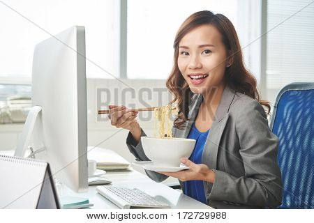 Happy female business executive having instant noodles for lunch