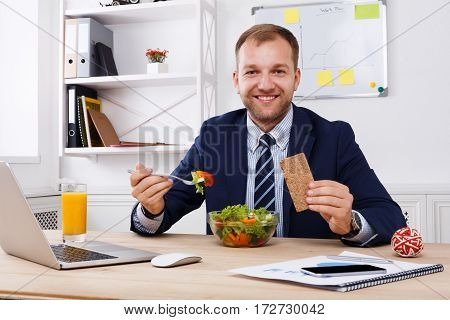 Man has healthy business lunch of vegetable salad in modern office. Young handsome businessman at working place, looking at camera, diet and eating right concept.
