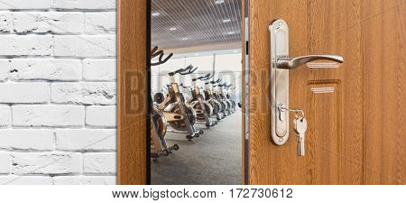 Opened door to modern gym interior with equipment. Entrance to fitness club with row of exercise stationery bikes for fitness cardio training. Welcome to sport, healthy lifestyle concept