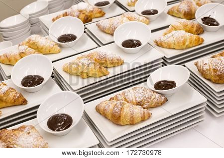 Modern White Plates With Plain Croissants With Chocolate Sauce. Buffet Set Up.