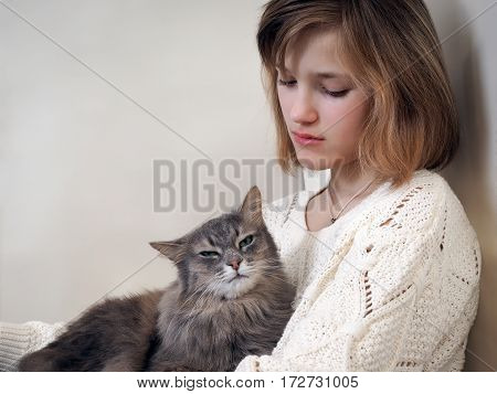Sad girl and gray cat. Light background