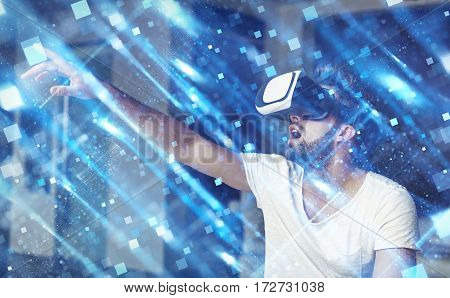 Young man with VR glasses playing virtual reality touching blue square polygons
