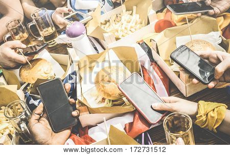 Group of multicultural friends having fun on smartphone at restaurant - Multiracial people hands using mobile smart phone at food sport bar - Technology addiction concept - Retro contrasted filter