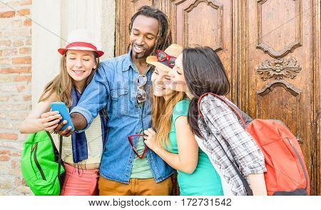 Group of happy multiracial friends taking selfie with mobile smart phone - Young hipster people addicted by smartphone on social network community - Technology concept - Vivid saturated filter tone