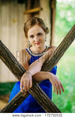 Young Overweight Girl At Blue Dress Posed Background Spring Garden On Wooden Hut.