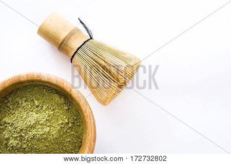 Matcha green tea in a bowl and bamboo whisk isolated on white background