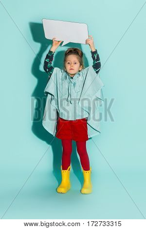 Little girl posing in fashion style wearing autumn clothing on blue background with empty blank. Rubber yellow boots.