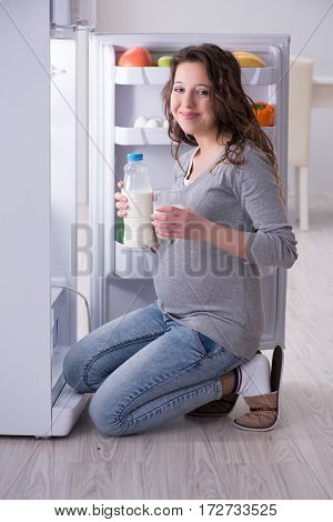 Pregnant woman near fridge looking for food and snacks