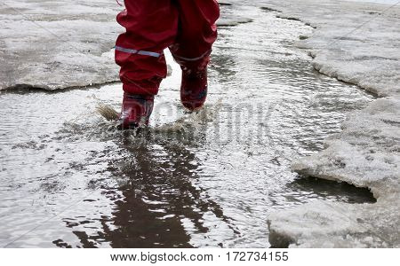 child in rain boots runs through the puddles in the early spring