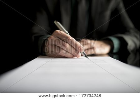 Closeup of lawyer or executive signing a contract placed on black desk.