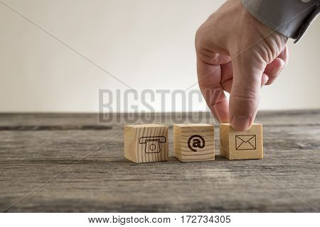Cubes with contact symbols - envelope at sign and telephone being placed on a rustic table by a businessman conceptual of communication and customer support.