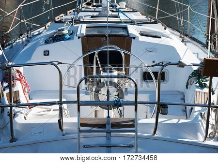Photo is taken from the back of a sailboat that is docked on a beautiful sunny day