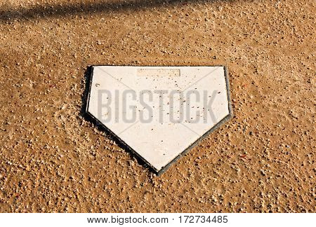 Home plate surrounded by dirt on a softball field