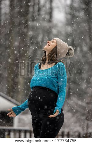 Pregnant woman in rolled up blue sweater and winter hat standing outside in snowfall with arms spread and head thrown back smiling enjoying weather.
