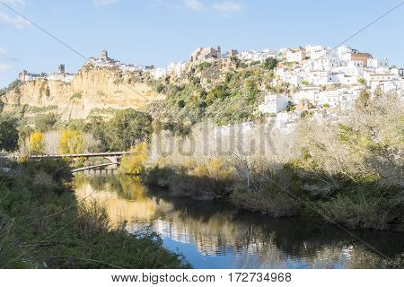 Panoramic of Arcos de la Frontera reflected in the river white town built on a rock along Guadalete river in the province of Cadiz Spain