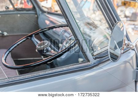 Bangkok Thailand -February 11 2017: Shiny retro wing mirror of classic beetle grey Volkswagen and blurred background of steering wheel inside.