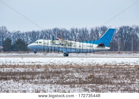 Kiev Region Ukraine - February 1 2011: Antonov An-140 regional passenger plane is taking off from the runway on a winter day