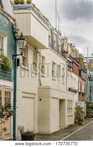 interesting facade of residential buildings typical English buildings at street style street lamps brick building covered in cream colored paint the architecture of the city