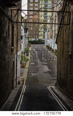 narrow passage to the streets with buildings low-rise buildings typical English narrow passage between the buildings on the square in the background a block of flats