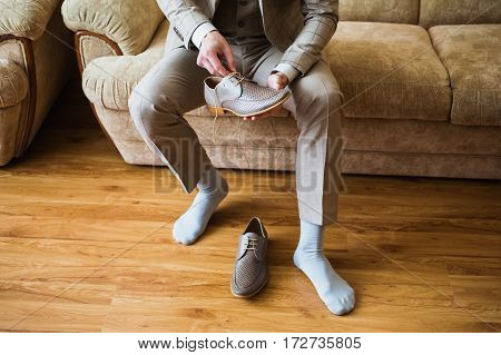 The man wears shoes. Tie the laces on the shoes. Men's style. Professions. To prepare for work to the meeting. Shoes on the floor