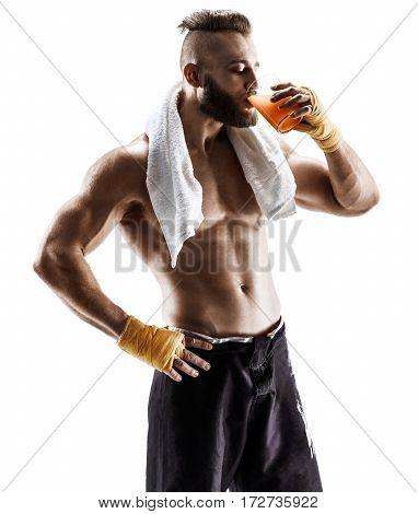Resting time. Handsome young man in sports wear wearing towel on his shoulders and drinks juice