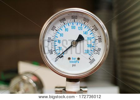 Row of metal steel high pressure gauge meters or manometers with brass fittings on tubing pipeline at LNG or LPG natural gas distribution station plant or factory facility isolated on white background.Pressure gauge in oil and gas production process