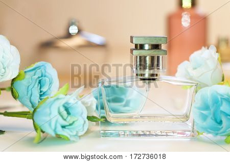 women's perfume bottle and a bouquet of roses on the table
