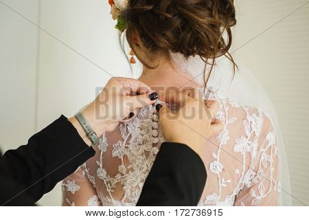 Buttoning wedding dress. Morning of the bride feminine style. Bridal Veil. Wedding gown