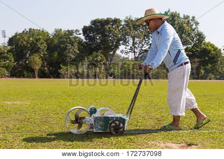 Chiang Mai Thailand - 28 December 2016 - Worker pushes paint roller to paint white line on soccer field at a soccer field in Chiang Mai Thailand on December 28 2016.