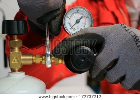 The officer turning valve on gas bottle